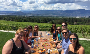A tour group enjoying the view over a picnic at Kitsch Wines in South Kelowna.